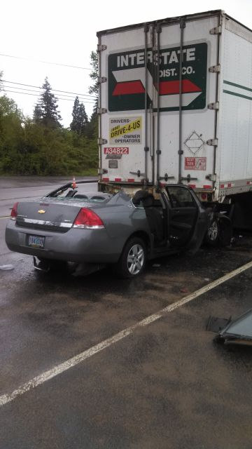 Driver injured when car crashes into rear of big rig stopped for train
