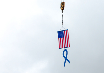 Flag and blue ribbon held aloft from crane