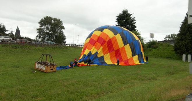 Hot air balloon lands safely near highway intersection