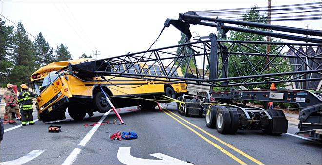 Driver pulled from school bus after collision with crane