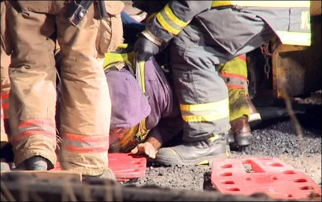 Injured worker pulled from under highway paving machine