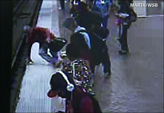 Bystanders save man who falls onto train tracks