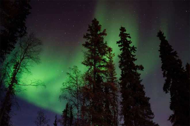 Northern Lights shine over Chandalar Lodge and Two Rivers Lodge.