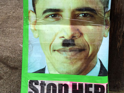 Protest signs compare Obama to Hitler