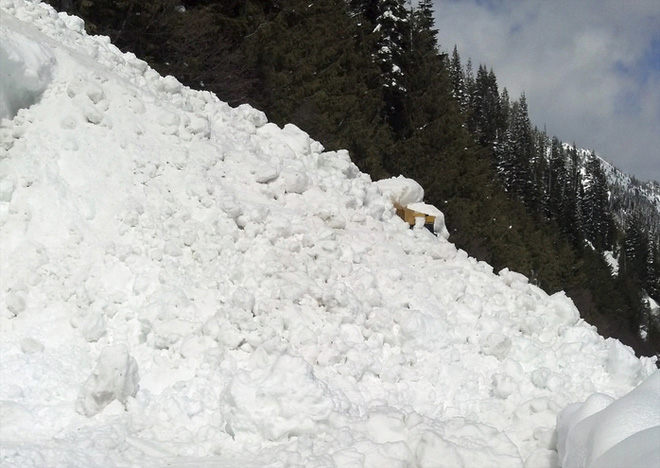 Avalanche traps road worker clearing mountain pass