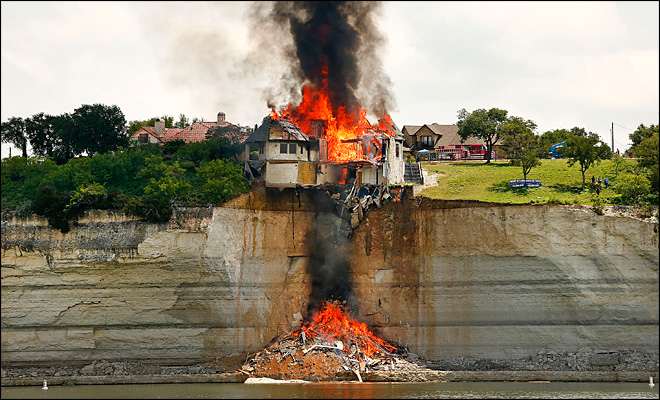 Crews burn house teetering on Texas cliff