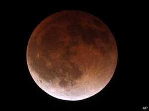 Photos: Eclipse tints moon a deeper shade of red