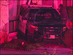 Police car rolls down hill, crashes into home