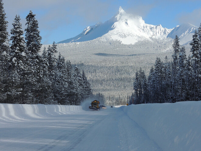 A snowplow clears Oregon 230 with Mt. Thielson in the background