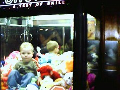 Young boy climbs into a claw game