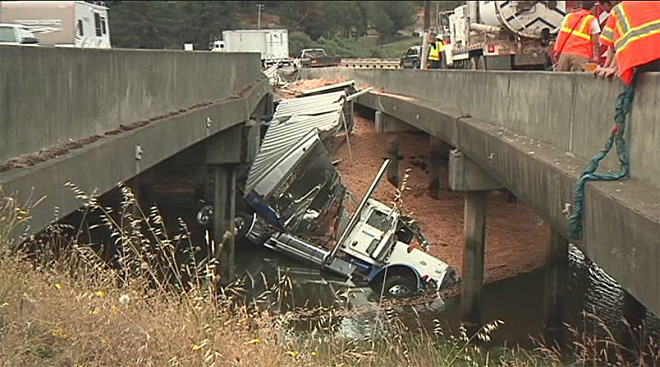 Truck crashes into slough, spilling diesel and wood chips