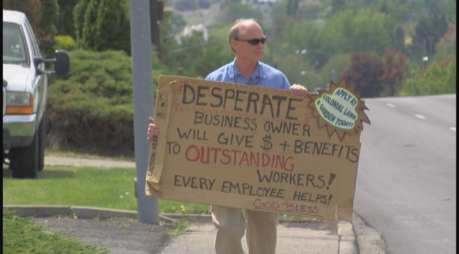 Panhandler in reverse: Businessman begs for workers on street