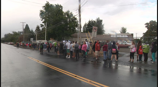 Families line up in rain for school supply giveaway
