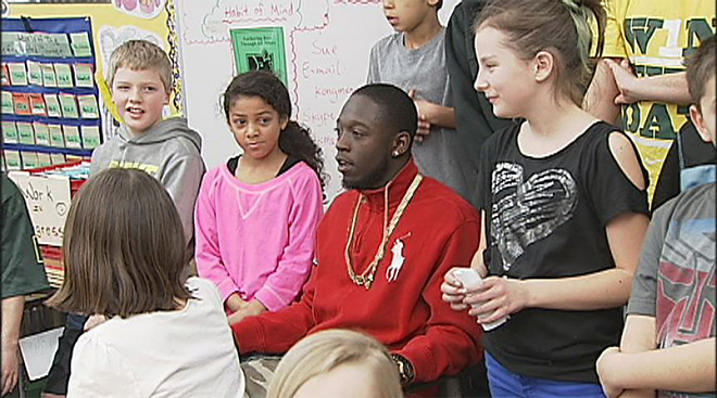 De'Anthony Thomas talks to children at McCornack Elementary