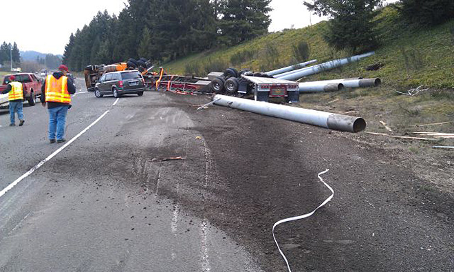 Truck overturns on I-5 off-ramp, spills pipes