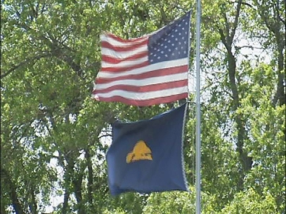 U.S. flag flown upsidedown, below state flag at public school