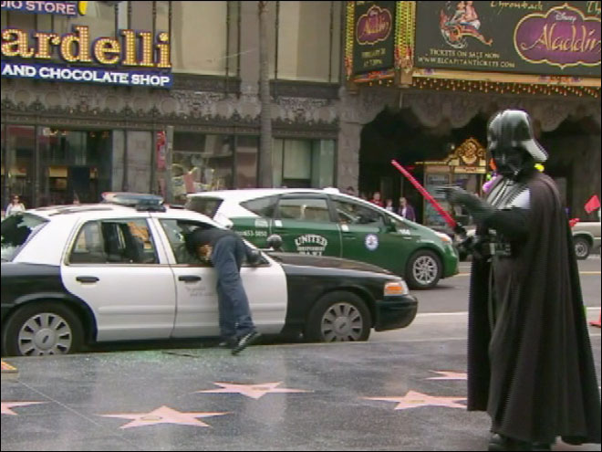 Darth Vader and Superman watch as cop car broken into