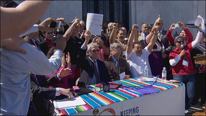 Immigrants cheer signing of driver's card bill
