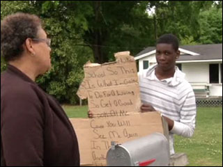 Boy forced to hold sign on street as punishment