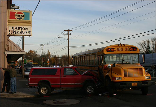 Child hurt when empty pickup rolls into school bus