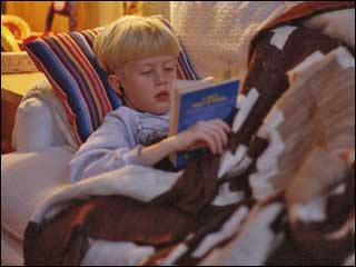 child laying on couch reading book